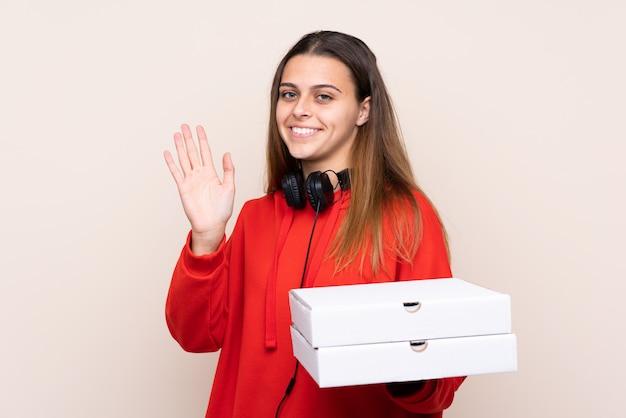 Ragazza di consegna della pizza che tiene una pizza sopra la parete isolata che saluta con la mano con l'espressione felice