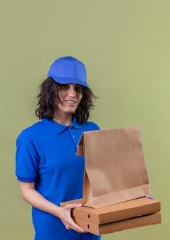 Ragazza di consegna in uniforme blu che tiene scatole per pizza e pacchetto di carta sorridente in piedi sicuro su uno spazio verde isolato