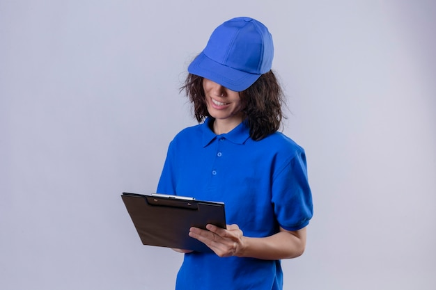 Ragazza di consegna in uniforme blu e cappuccio che tiene appunti guardandolo sorridente in piedi sicuro