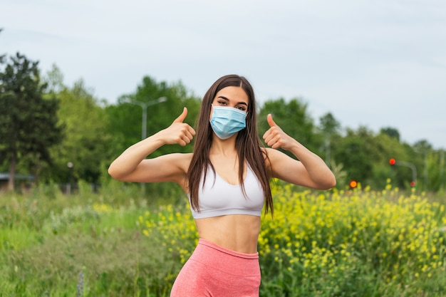 Ragazza di forma fisica, giovane donna in maschera medica sterile protettiva sul viso guardando la fotocamera un pollice mostrando segno. pronto ad allenarti durante la covida 19, pandemia di coronavirus