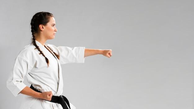 Ragazza di karatè di arti marziali con il fondo dello spazio della copia e della cintura nera