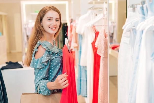 Ragazza di moda che controlla camicetta e sorridente