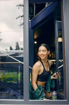 Ragazza di moda in piedi in un caffè estivo