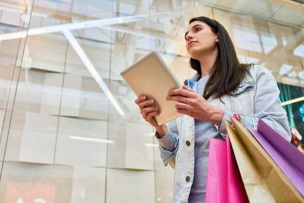 Ragazza di moda pensieroso trovare negozio nel centro commerciale