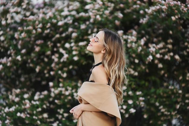 Ragazza di modello bionda alla moda e sensuale con un bel sorriso in cappotto senza maniche e occhiali da sole alla moda