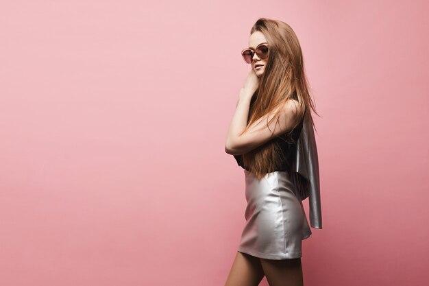 Ragazza di modello bionda bella e alla moda in camicetta nera e in una gonna d'argento in posa nello studio
