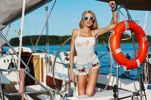 Ragazza di modello bionda con l'ente esile perfetto in pantaloncini corti e maglietta che posa su una nave dell'yacht