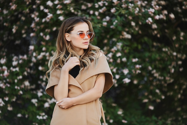Ragazza di modello bionda in cappotto senza maniche e in occhiali da sole alla moda che posano all'aperto