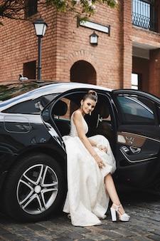 Ragazza di modello bruna con le gambe lunghe con trucco luminoso in un vestito d'argento alla moda si siede nell'auto di lusso