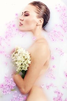 Ragazza di modello di bellezza della stazione termale che bagna nel concetto del bagno di latte, della stazione termale e di cura di pelle. bellezza giovane donna con corpo perfetto slim e pelle morbida, in ghirlanda di fiori rilassante nel bagno di latte.