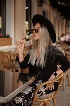 Ragazza di modello in occhiali da sole e vino bevente black hat al caffè della tavola sulla via, colpo di modo di estate.