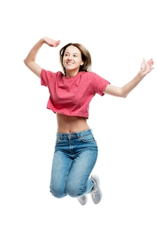 Ragazza di salto di risata dei giovani in canottiera sportiva e jeans rossi. tempo felice. . verticale.