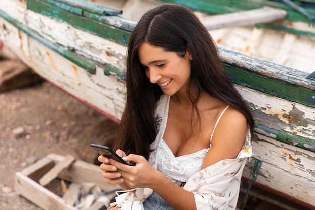 Ragazza di smiley ad alto angolo con lo smartphone