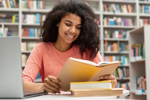 Ragazza di smiley alla biblioteca che studia e che per mezzo del computer portatile