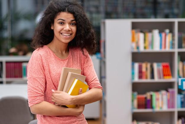 Ragazza di smiley alla biblioteca il giorno del libro del mondo