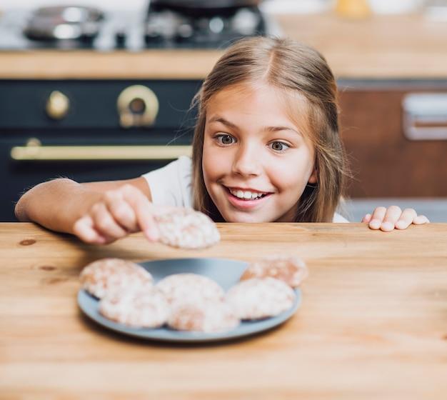 Ragazza di smiley che cattura un biscotto delizioso