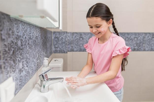 Ragazza di smiley che lava le sue mani