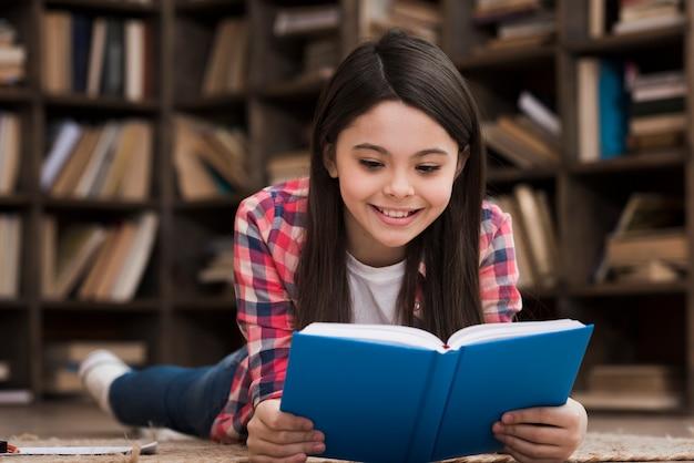 Ragazza di smiley che legge un romanzo