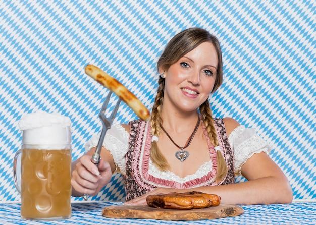 Ragazza di smiley che presenta salsicce bavaresi