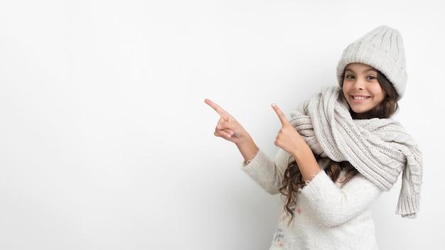 Ragazza di smiley con indicare della sciarpa e del cappello