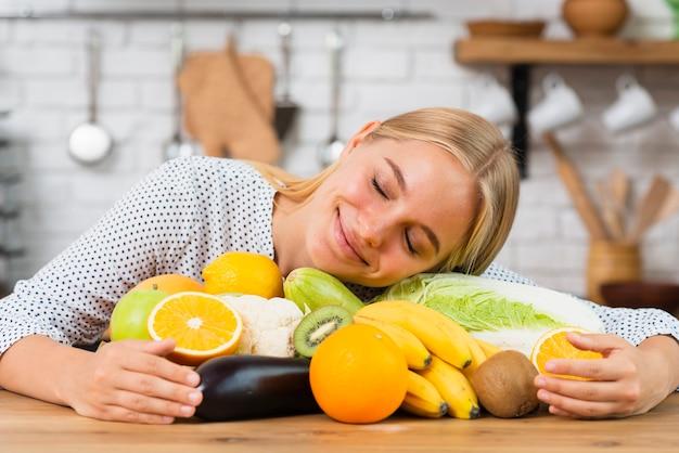 Ragazza di smiley del colpo medio che abbraccia la frutta fresca