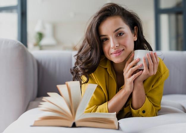 Ragazza di smiley del colpo medio con il libro e la tazza