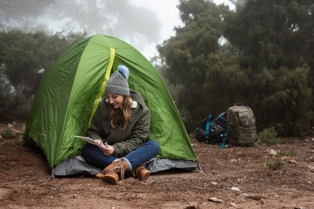 Ragazza di smiley della foto a figura intera che si siede vicino alla tenda