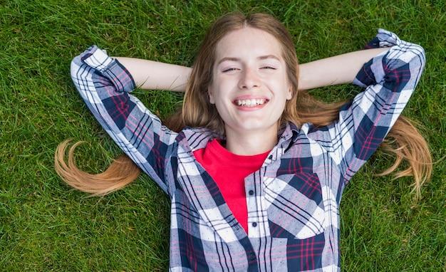 Ragazza di smiley di vista superiore che resta sull'erba