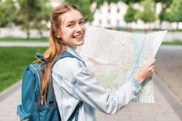 Ragazza di smiley nel parco usando una mappa