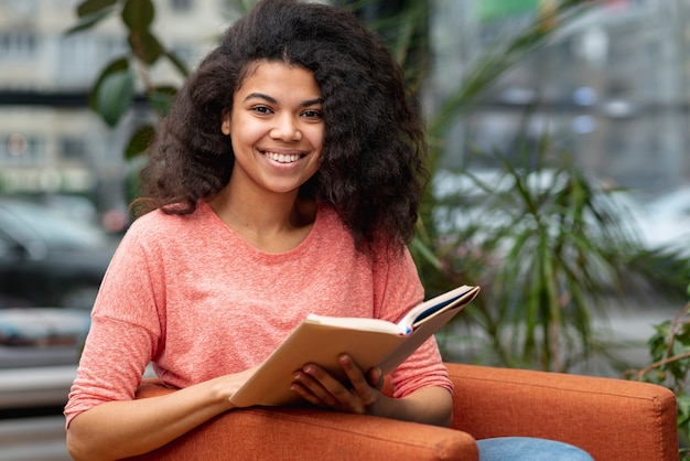 Ragazza di smiley sulla lettura della poltrona
