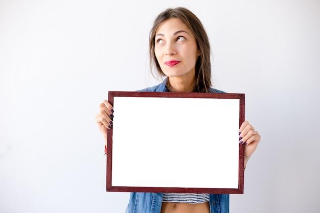 Ragazza di sogno del primo piano con un cartello o un manifesto bianco in bianco