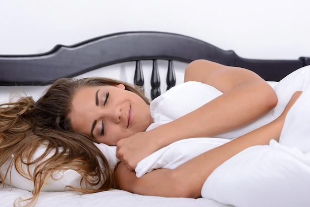 Ragazza di sorriso che dorme nel letto nella sua camera da letto.