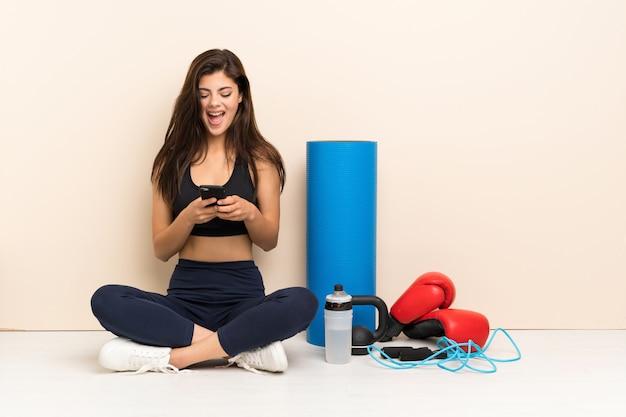 Ragazza di sport dell'adolescente che si siede sul pavimento che invia un messaggio con il cellulare