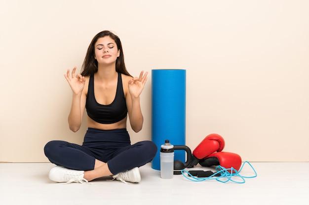 Ragazza di sport dell'adolescente che si siede sul pavimento nella posa di zen