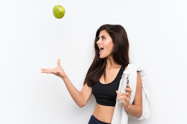 Ragazza di sport dell'adolescente sopra bianco isolato con una mela e una bottiglia di acqua