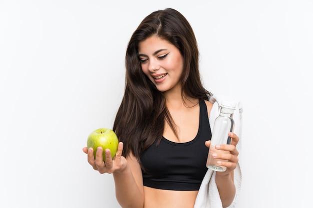 Ragazza di sport dell'adolescente sopra fondo bianco isolato con una mela e una bottiglia di acqua