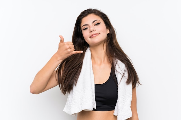 Ragazza di sport dell'adolescente sopra la parete bianca isolata che fa gesto del telefono