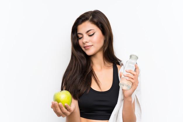 Ragazza di sport dell'adolescente sopra la parete bianca isolata con una mela e una bottiglia di acqua