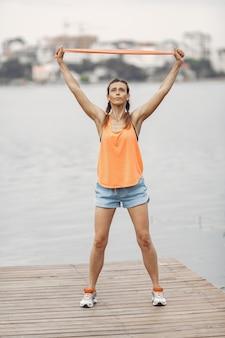 Ragazza di sport sull'acqua. donna in un parco estivo. signora in abiti sportivi arancioni.