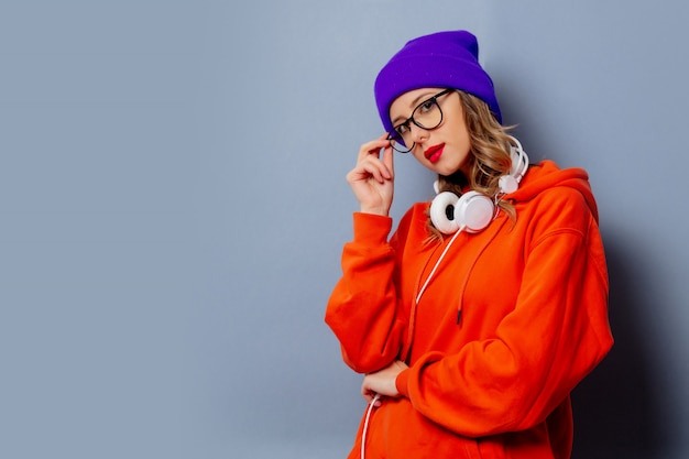 Ragazza di stile in felpa con cappuccio arancione e cappello viola con le cuffie sulla parete grigia