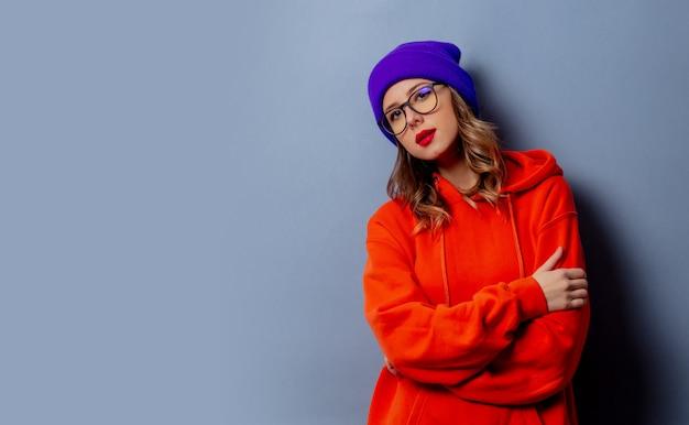 Ragazza di stile in felpa con cappuccio arancione e cappello viola sulla parete grigia