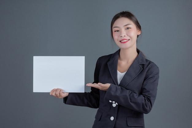 Ragazza di ufficio che tiene una scheda in bianco bianca