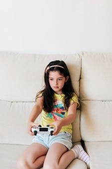 Ragazza di vista frontale che gioca i videogiochi