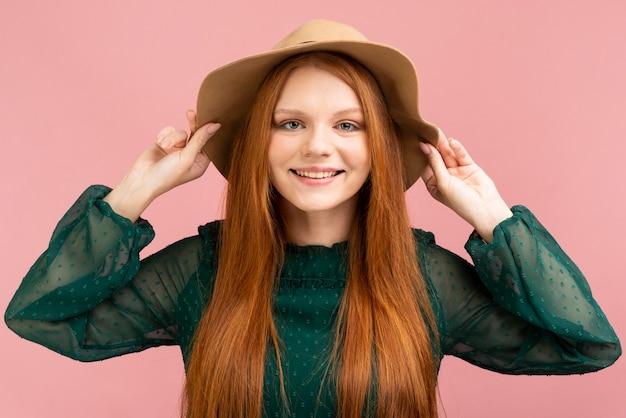Ragazza di vista frontale che propone con il cappello