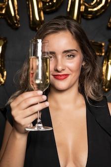 Ragazza di vista frontale che tiene un bicchiere di champagne
