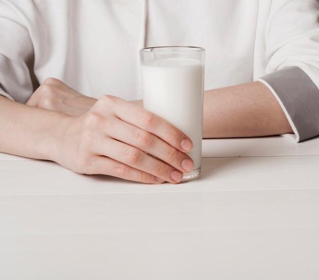 Ragazza di vista frontale che tiene un bicchiere di latte