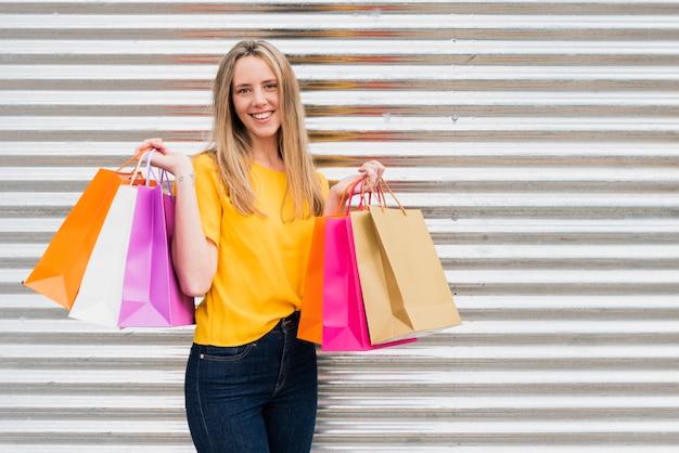 Ragazza di vista frontale con i sacchetti della spesa