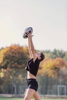 Ragazza di vista laterale che prende una palla di rugby