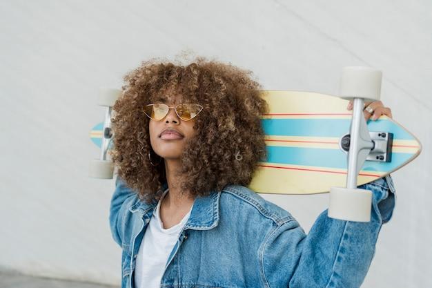 Ragazza di vista laterale con skateboard