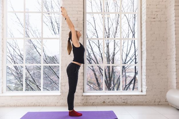 Ragazza di yoga da solo nella stanza di yoga dalla finestra al mattino in piedi con le mani in alto